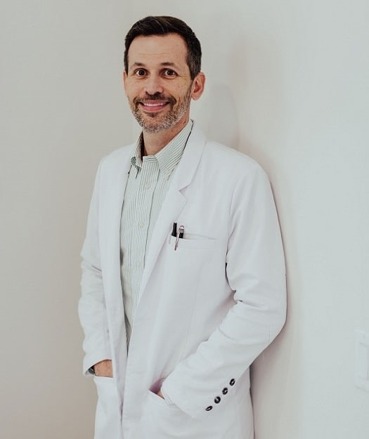 Dr Walters standing in front of a white background.